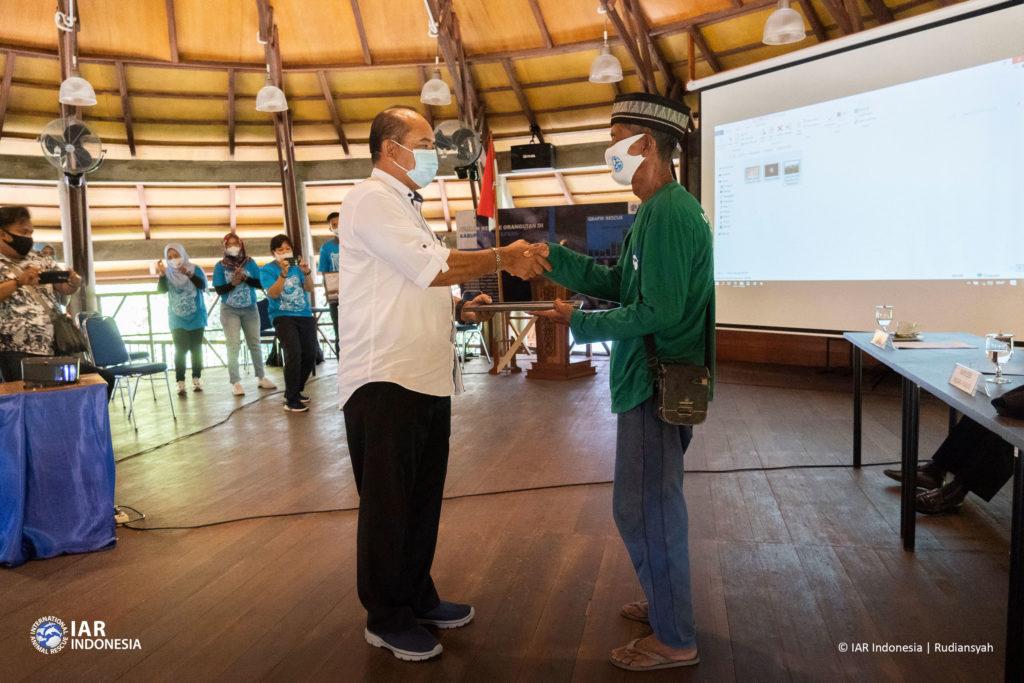 Adi Mulya (kiri) saat memberikan penghargaan Pahlawan Langit Biru Tanpa Asap kepada Sujana (kanan) di Pusat Pembelajaran Sir Michael Uren Ketapang.